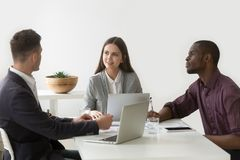 Multiracial colleagues cooperating working on laptops and tablet royalty free stock image