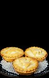 Three mince pies against a black background. Three homemade mince pies surrounded by edible silver balls against a black background stock images