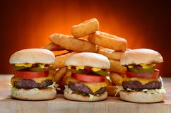 Three Mini Cheeseburger Sliders with Onion Rings Stock Photo