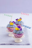 Three mini cupcakes. With buttercream topping and edible pansies royalty free stock image