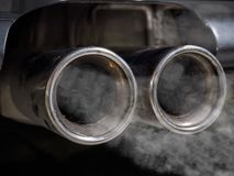 Miniature people examining car exhaust royalty free stock images