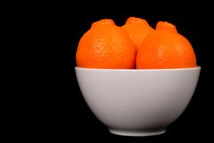 Three minneola oranges in white bowl. Three sweet minneola oranges in white bowl Stock Photos