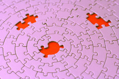 Three missing pieces in a pink jigsaw. Focus is on the center hole - adobe RGB Stock Image