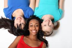 Three mixed race teenage girl friends on floor stock photo
