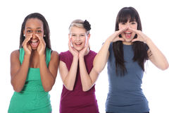 Three mixed race teenage girls shouting out loud. Shouting out loud are three pretty young teenager girl friends a blonde caucasian student, an oriental Japanese Royalty Free Stock Image