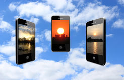 Three mobile phones with different sunsets Stock Image