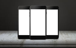 Three mobile phones on table with isolated display for mockup Stock Images