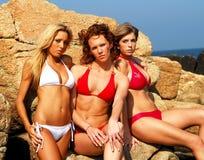 Three models in bikinis. Three models pose on rocks royalty free stock photos