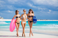 Three models on a tropical beach with a circle. Three young beautiful girls - brunette with long straight hair in black and white bikini, wearing sun glasses Royalty Free Stock Photos