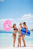 Three models on a tropical beach with a circle. Three young beautiful girls - brunette with long straight hair in black and white bikini, wearing sun glasses Stock Image