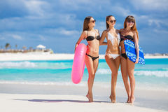 Three models on a tropical beach with a circle. Three young beautiful girls - brunette with long straight hair in black and white bikini, wearing sun glasses Stock Photo
