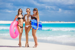 Three models on a tropical beach with a circle. Three young beautiful girls - brunette with long straight hair in black and white bikini, wearing sun glasses Stock Photography
