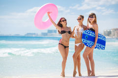 Three models on a tropical beach with a circle. Three young beautiful girls - brunette with long straight hair in black and white bikini, wearing sun glasses Royalty Free Stock Image