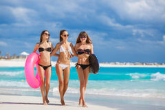 Three models on a tropical beach with a circle. Three young beautiful girls - brunette with long straight hair in black and white bikini, wearing sun glasses Royalty Free Stock Images