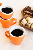 Three modern coffee cups with plates of sweets Royalty Free Stock Images