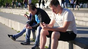 Three modern friends communicate in the park, sit with phones in the hands on the Internet. SLOW MOTION. HD, 1920x1080. stock video