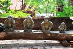 Three monkey statue sit on nature background and hand small statues with the concept of see no evil, hear no evil and speak no royalty free stock photos