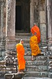Three monks walking into the temple stock photography