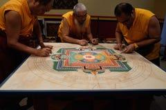 Three Monks working on Mandala Stock Photos
