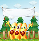 Three monsters under the empty banner Royalty Free Stock Photography