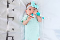 A three month baby girl in mint green clothes lying on a bed on which a measuring ruler for growth is drawn. Teething tool in
