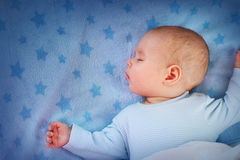 Three month old baby sleeping on blue blanket Royalty Free Stock Photo