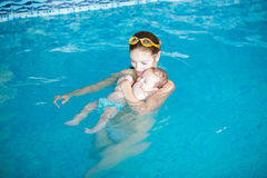 Three months baby relaxing in the swimming pool with mother Royalty Free Stock Images