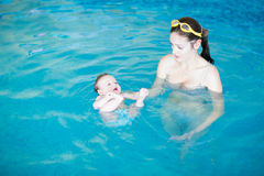 Three months baby relaxing in the swimming pool with mother. Three months baby relaxing in the swimming pool with her mother Stock Image