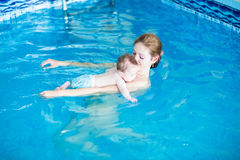 Three months baby relaxing in the swimming pool with mother Royalty Free Stock Photos