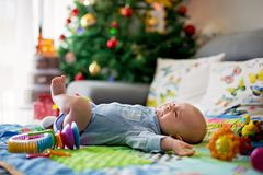 Three months old baby boy, crying at home on a colorful activity. Blanket, toys and different activity around him Royalty Free Stock Photo
