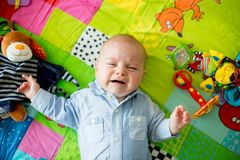 Three months old baby boy, crying at home on a colorful activity. Blanket, toys and different activity around him Royalty Free Stock Images