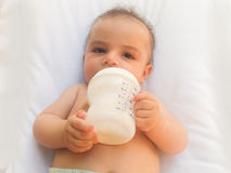 Three months old baby boy drinking milk from the bottle Royalty Free Stock Photos