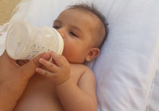 Three months old baby boy drinking milk from the bottle royalty free stock photo