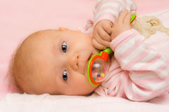 Three months old infant. Three months old infant playing with her rattle Stock Photos