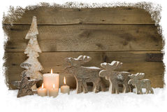 Three mooses wearing santa hats on grey wooden background Royalty Free Stock Photos