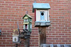 Three more bird houses on posts. With a brick wall background Royalty Free Stock Image