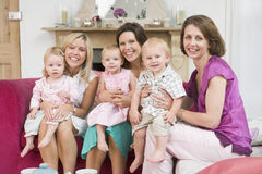 Three mothers in living room with babies royalty free stock image