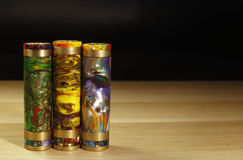 Three motley multicolored mechanical mods for vaping electronic cigarette on the wooden surface on black background close up Stock Photos