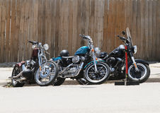 Three motorcycles parked by wooden fence Royalty Free Stock Photos