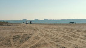 Three motorcyclists riding near sandy beach in desert from far away. Biker ride. stock footage