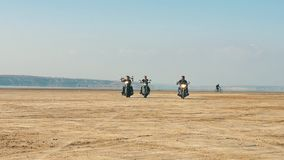 Three motorcyclists riding near sandy beach in desert from far away. Free ride. stock video