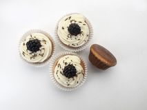 Three muffins decorated with buttercream and raspberries top view stock photo
