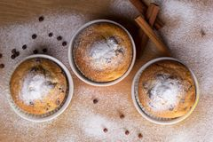 Three muffins with icing sugar. And chocolate balls Royalty Free Stock Images