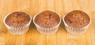 Three muffins in row on wooden board Royalty Free Stock Photography