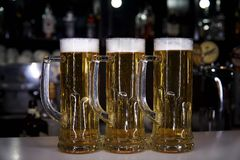 Three mugs with a cold beer. On the background of a blurry bar royalty free stock photos