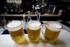 Three mugs of cold beer. Stand on the bar royalty free stock photos
