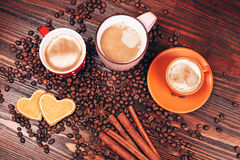 Three mugs full of hot coffee. View from above of closely packed mugs full of hot coffee with foam, cinnamon sticks, star anise, coffee beans and wooden board Royalty Free Stock Photo