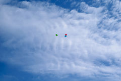 Three multi-colored balloons fly in the blue sky with clouds Stock Photos