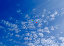 Three multi-colored balloons fly in the blue sky with clouds Stock Photo