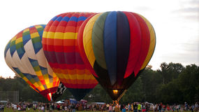Three Multi-Colored Balloons A'Glow. Colorful balloons, fully inflated, tethered to the ground fire their burners at the 2nd Annual Color Aloft Balloon Fest in Royalty Free Stock Images